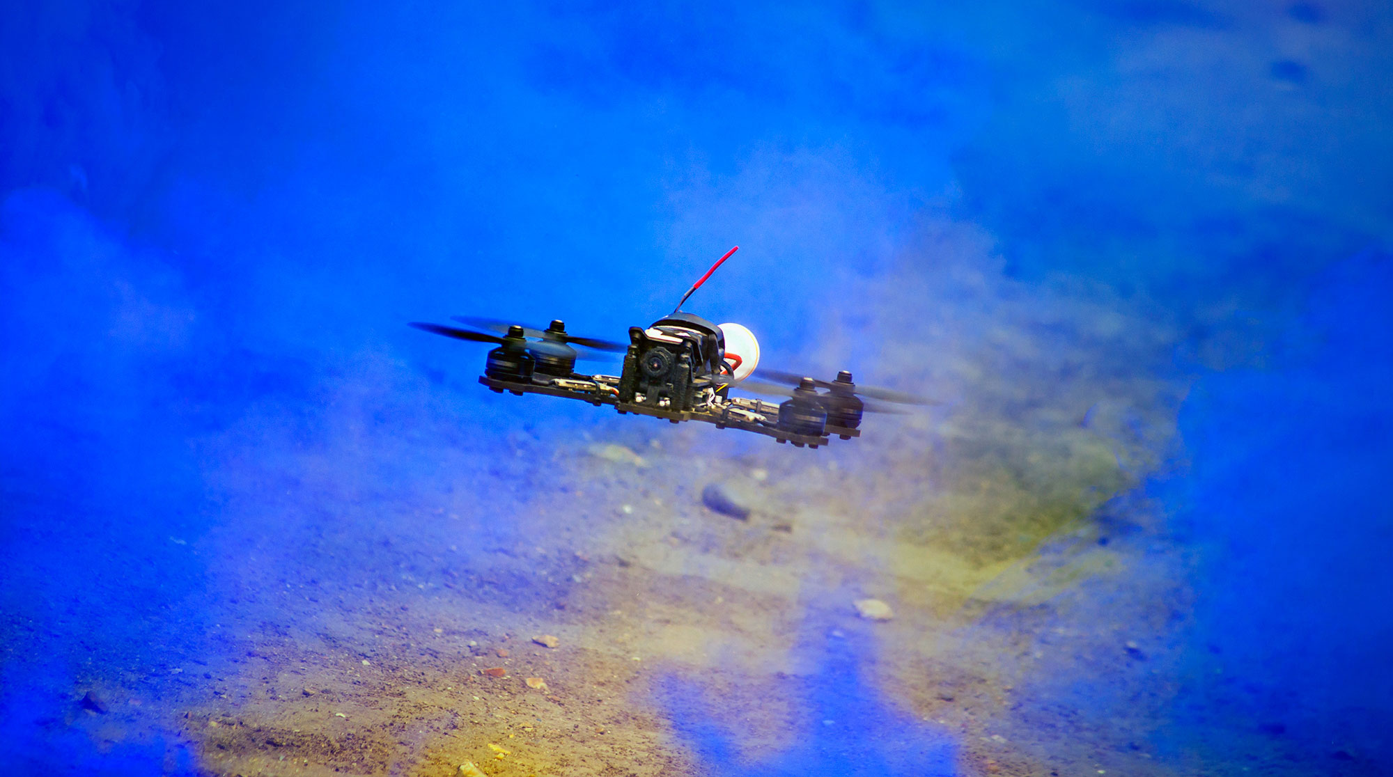 Quadcopter flying through blue smoke