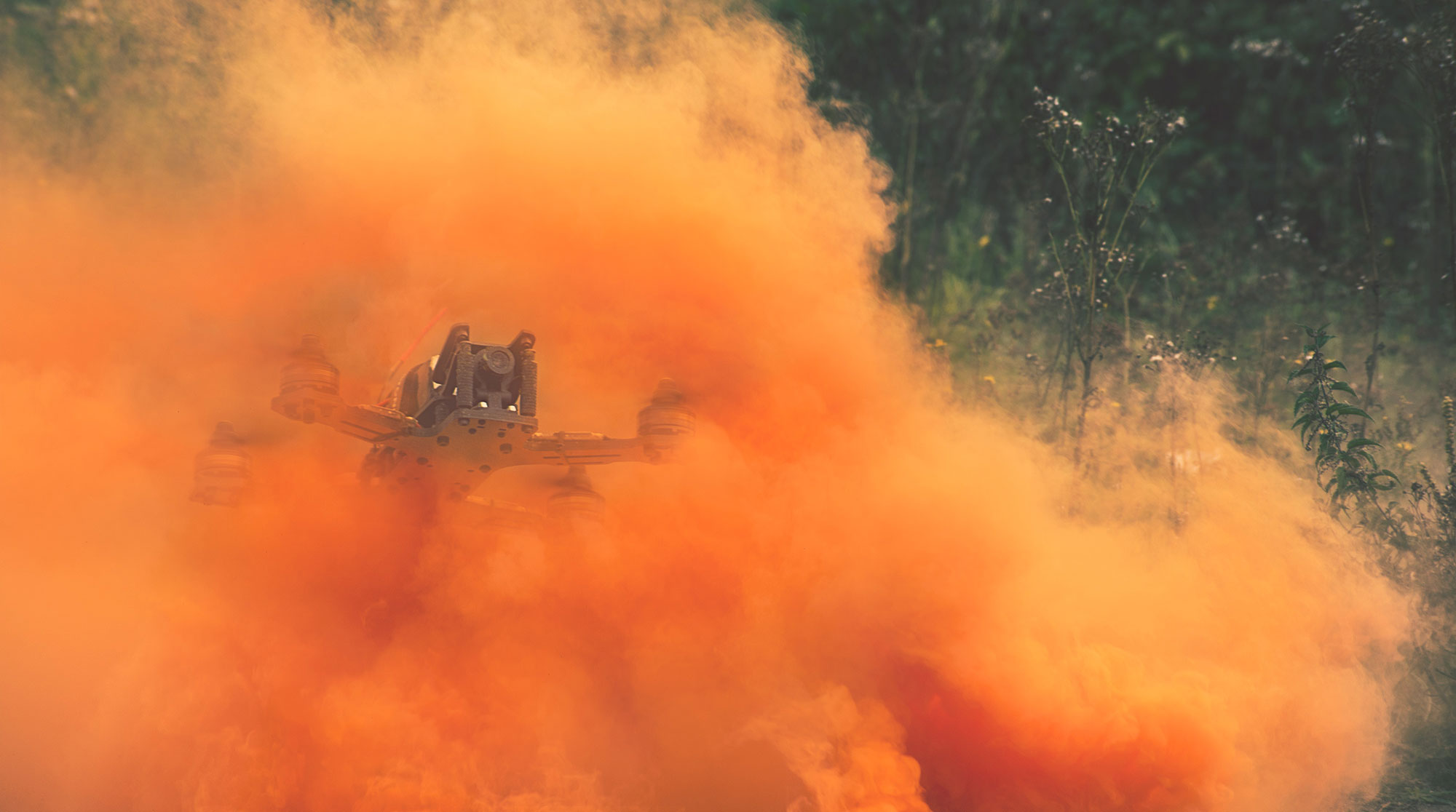 Quadcopter flying through orange smoke